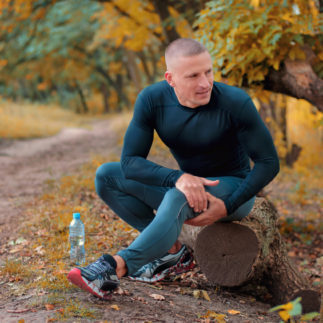 A young athletic  jogger in black tight fitting sportswears and  sneakers sits on a log, is in pain and holding a hip with his hands after cramping on a autumnall forest background.