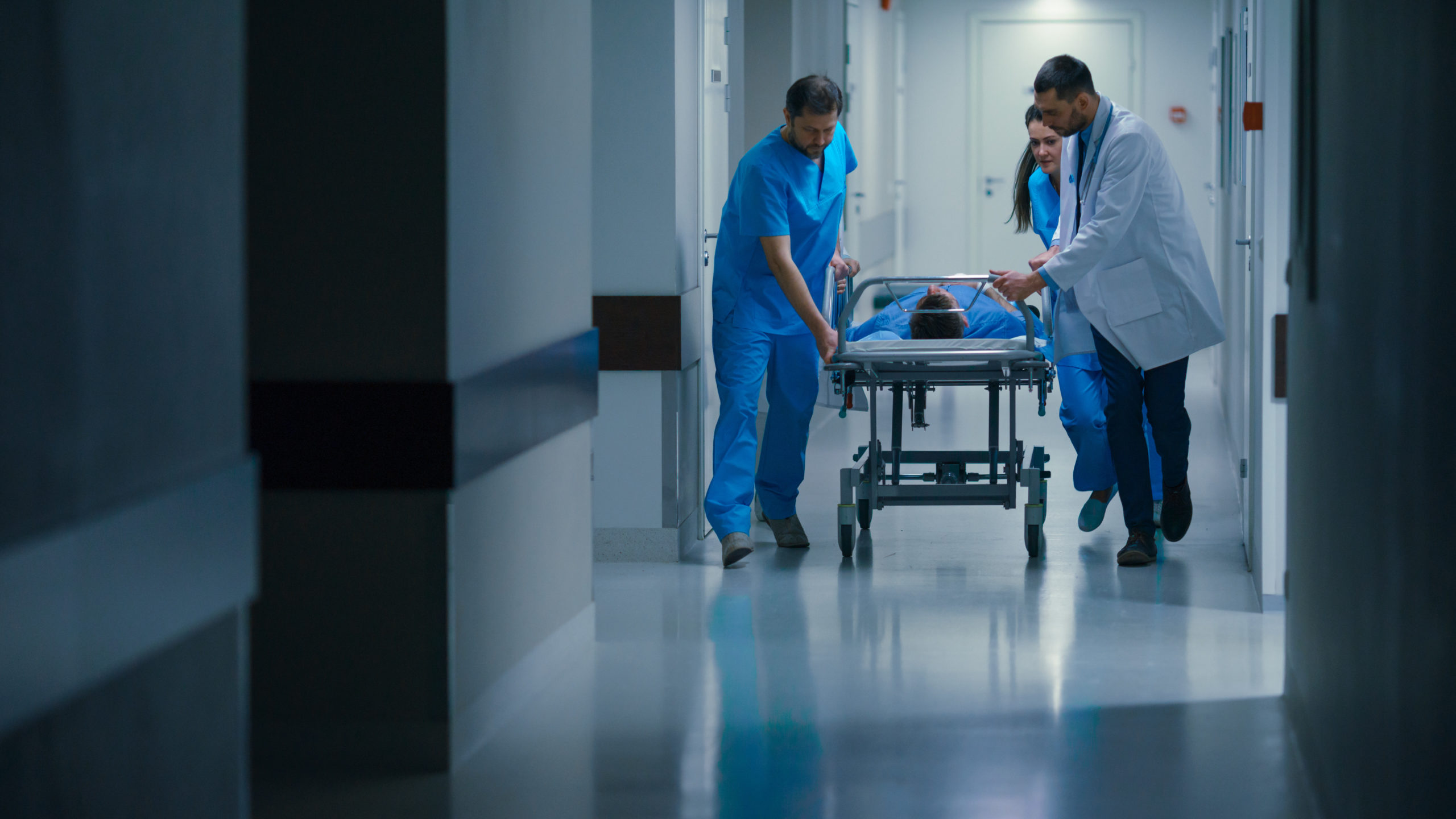Emergency Department: Doctors, Nurses and Paramedics Push Gurney / Stretcher with Seriously Injured Patient towards the Operating Room. Bright Modern Hospital with Professional Staff Saving Lives.