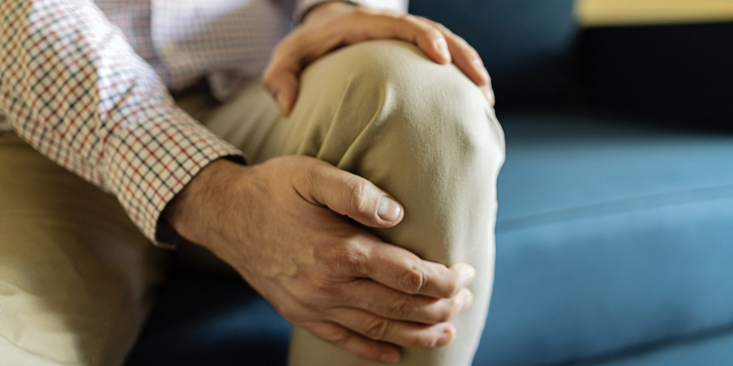 A Mature Man Massaging His Painful Knee. Man Suffering From Knee Pain At Home, Closeup. Pain Knee